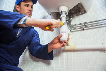 Frowning plumber repairing sink in public bathroom